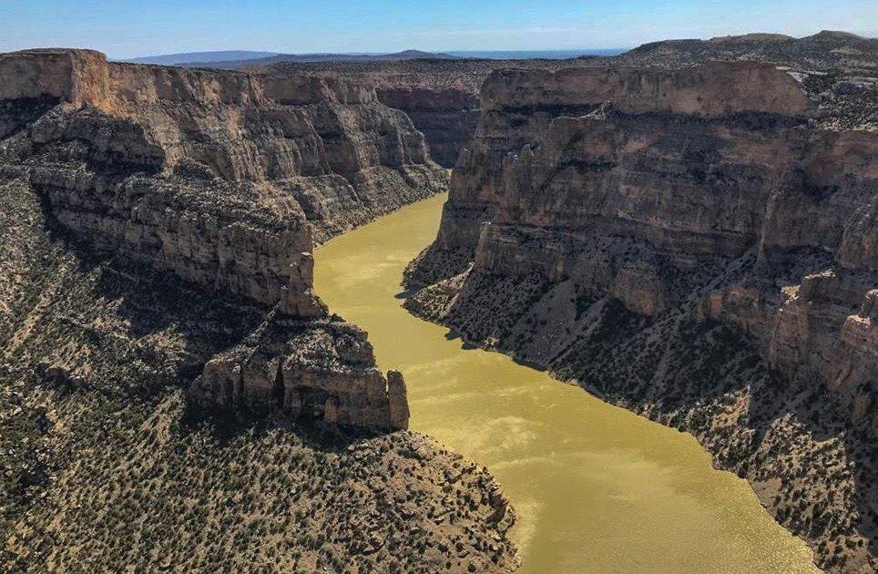 un fiume color verde oliva scorre in fondo ad un canyon formato da rocce a picco sul fiume. le rocce sono di colore beige, verde e rosate