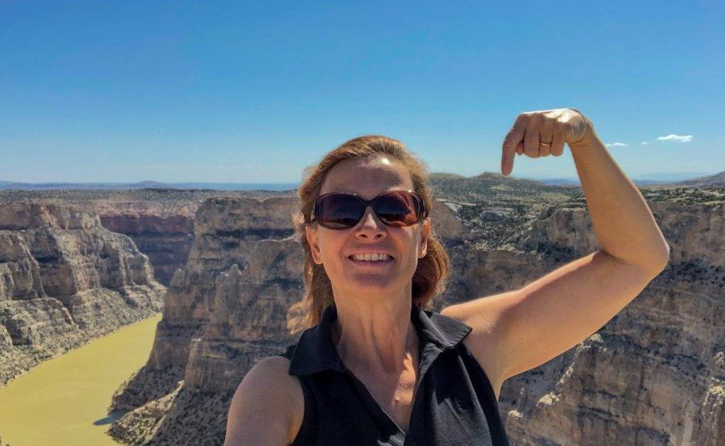 In rimo piano una donna a mezzo busto con capelli lunghi rosso-castano e occhiali da sole. Alle sue spalle Il Bighorn Canyon in Wyoming, con le rocce grigie e rosa e sul fondo del canyon il fiume bighorn color verde oliva.