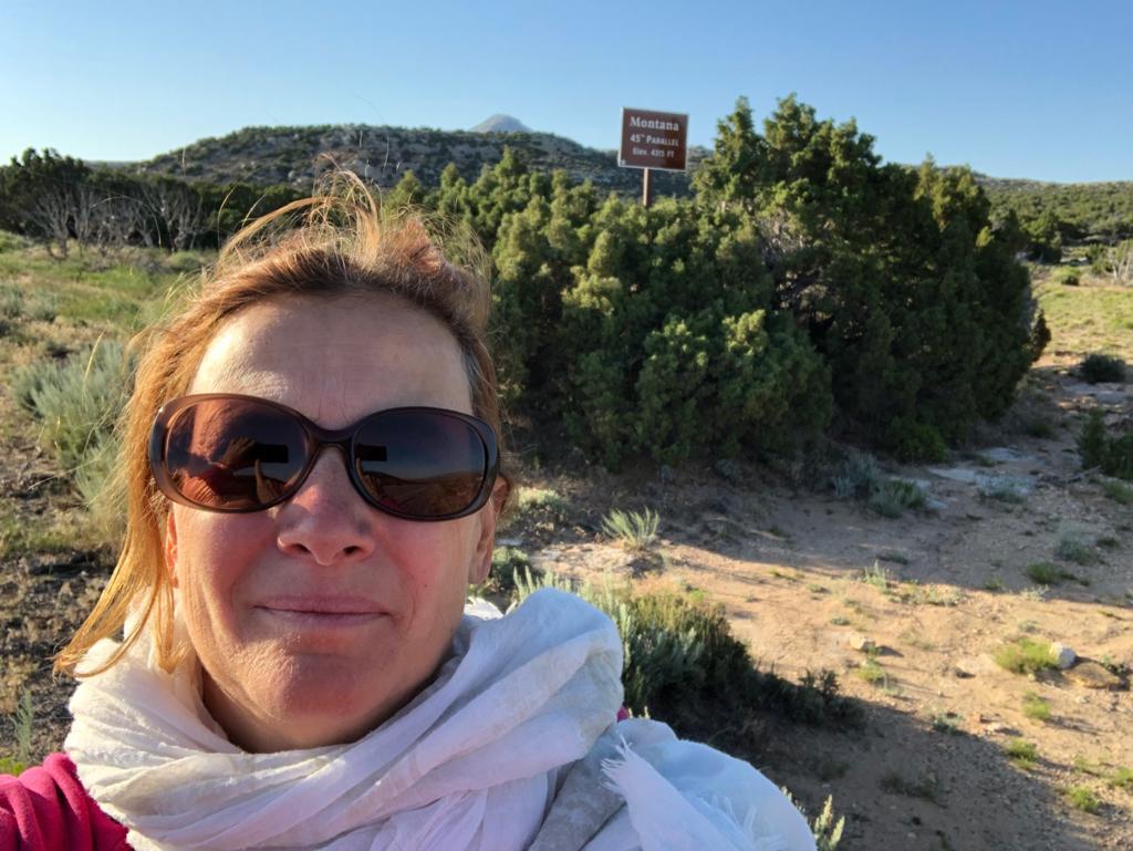Una donna in primo piano con i capelli raccolti e occhiali da sole, con una sciarpa bianca al confine tra Montana e Wyoming nel Bighorn Canyon. Alle sue spalle il cartello che indica il confine del Montana