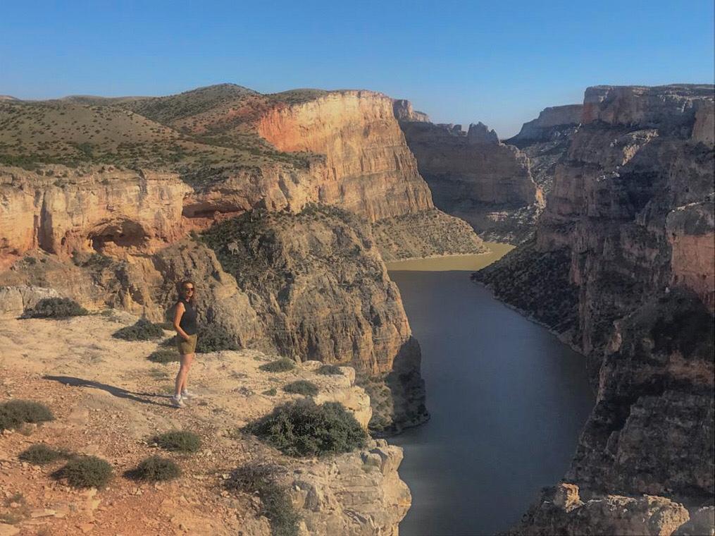Il Bighorn canyon in Wyoming visto dall'alto. Sul fondo il fiume Bighorn scorre color verde oliva.Sulla destra la scogliera a picco sul fiume di rocce rosa beige e verdi. sulla sinistra il promontorio di roccia rosa e beige con ciuffi verdi di vegetazione. a figura intera una donna con pantaloncini verdi e maglietta smanicata blu. Hai capelli lunghi rosso castano e gli occhiali da sole.