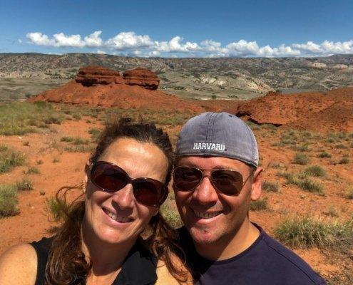 una coppia sui cinquantanni in primo piano. Entrambi indossano una maglietta blu e occhiali da sole. Lui anche un cappellino blu al contrario. Sullo sfondo due rocce gemelle rosse. Tutto intorno terra rossa e cespugli verdi. il cielo è azzurro con delle nuvolette bianche
